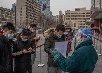 Εργαζόμενη σε νοσοκομείο του Πεκίνου, φορώντας προστατευτικό εξοπλισμό, ελέγχει πολίτες που φθάνουν εκεί για να ελεγχθούν για Covid-19. Εικόνες σαν κι αυτή είναι καθημερινές σε όλη την Κίνα (φωτ.: EPA/ROMAN PILIPEY)