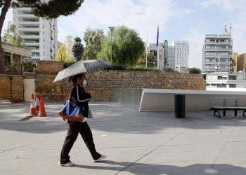 Γυναίκα που φορά προστατευτική μάσκα για τον κορονοϊό περπατα στη Λευκωσία (φωτ.:EPA / Katia Christodoulou)