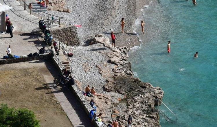 Κόσμος απολαμβάνει τον καλό καιρό και το μπάνιο του στην παραλία της Αρβανιτιάς στο Ναύπλιο (φωτ.: ΑΠΕ-ΜΠΕ / Ευάγγελος Μπουγιώτης)