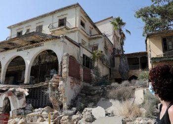Γυναίκα στέκεται μπροστά από μισοκατεστραμμένο κτήριο στο κέντρο των Βαρωσίων στην Κύπρο (φωτ. αρχείου: EPA / Κάτια Χριστοδούλου)
