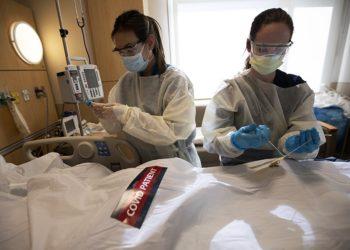 Οι νοσηλεύτριες Έιπριλ ΜακΦάρλαντ και Τίφανι Ρόμπινς κλείνουν τη σορό ενός θύματος του κορονοϊού σε λευκό σάκο, στο Ιατρικό Κέντρο Πρόβιντενς Χόλι Κρος στο Μίσιον Χιλς της Καλιφόρνιας (φωτ.: Los Angeles Times / Francine Orr)