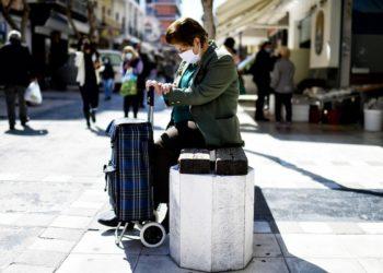 Μία γυναίκα, φορώντας προστατευτική μάσκα για τον κορονοϊό, κάθεται σ΄ ένα παγκάκι στο κέντρο της Κορίνθου (φωτ.: ΑΠΕ-ΜΠΕ /Βασίλης Ψωμάς)