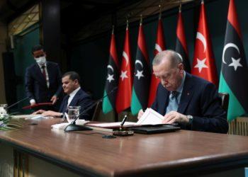 Ο πρωθυπουργός της Κυβέρνησης Εθνικής Ενότητας της Λιβύης, Αμπντέλ Χαμίντ Νπμπέιμπα υπογράφει κάποια συμφωνία με τον Ρετζέπ Ταγίπ Ερντογάν, στο προεδρικό μέγαρο στην Άγκυρα (φωτ.:  EPA/ TURKISH PRESIDENT PRESS OFFICE HANDOUT)