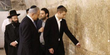 Ο Ισραηλινός πρωθυπουργός Μπενιαμίν Νετανιάχου και ο γιος του Γέαρ αφήνουν σημείωμα στο Δυτικό Τείχος, στην Ιερουσαλήμ (φωτ.: EPA/ABIR SULTAN)