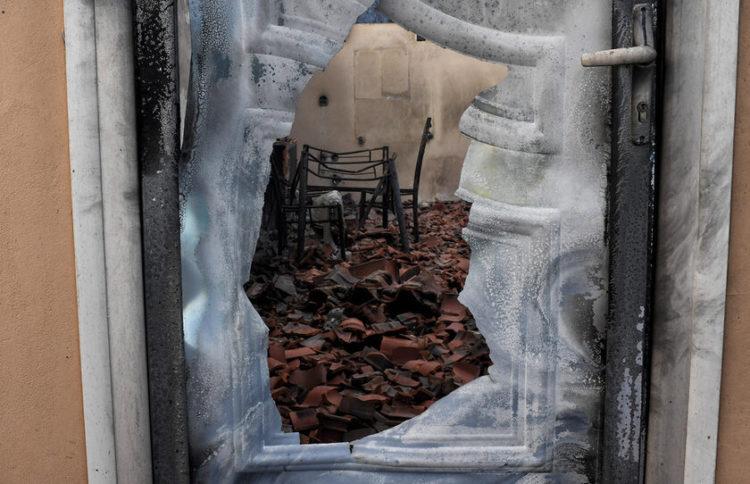 Καμένο σπίτι από την πυρκαγιά που είναι σε εξέλιξη στην περιοχή Σχίνος Λουτρακίου (φωτ.: ΑΠΕ-ΜΠΕ/ Βασίλης Ψωμάς)