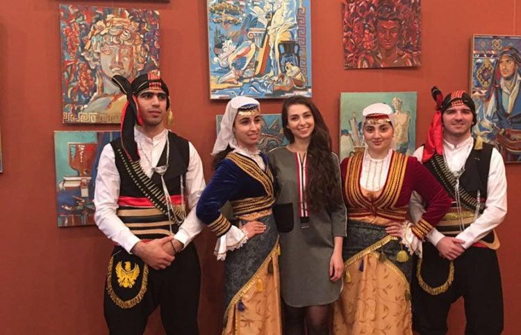 Η Νίνα Ιωαννίδη ποζάρει με φόντο τους πίνακές της και μέλη του χορευτικού συγκροτήματος «Πόντος», στα εγκαίνια έκθεσής της στο Κρασνοντάρ, τον Μάρτιο του 2018 (φωτ.: rusgreek.ru)