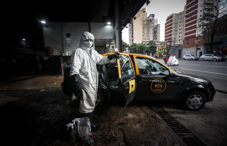 Προσωπικό απολυμαίνει ένα ταξί (φωτ.: EPA/Juan Ignacio Roncoroni)