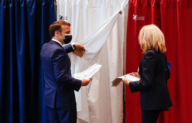 Ο πρόεδρος της Γαλλίας Εμμανουέλ Μακρόν με τη σύζυγο του Μπριζίτ την ώρα που ψηφίζει (φωτ.: ΕPA/ Christian Hartmann)