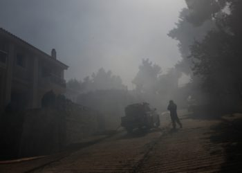 Πυροσβέστης μέσα σε κατοικημένη περιοχή επιχειρεί στην κατάσβεση της πυρκαγιάς που ξέσπασε σε δασική περιοχή στη Σταμάτα, Αττικής (φωτ.: ΑΠΕ-ΜΠΕ / Γιάννης Κολεσίδης)