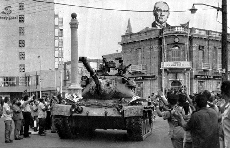 24 Ιουλίου 1974. Ένα τουρκικό τανκ περνάει μπροστά απ' το Saray Hotel στο κατεχόμενο μέρος της Λευκωσίας. Στην οροφή του διπλανού κτηρίου διακρίνεται πανό με τον Μουσταφά Κεμάλ (φωτ.: αρχείο Associated Press)