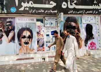 Αφγανοί περνούν μπροστά από σαλόνι ομορφιάς, στην Καμπούλ, όπου τα πρόσωπα των μοντέλων στις αφίσες έχουν παραμορφωθεί (φωτ.: EPA/STRINGER)