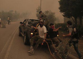 Πολίτες επιβιβάζονται σε υδροφόρο όχημακατά τη διάρκεια της επιχείρησης κατάσβεσης της πυρκαγιάς,στο Πευκί, στη βόρεια Εύβοια (φωτ.:: ΑΠΕ-ΜΠΕ/Κώστας Τσιρώνης)