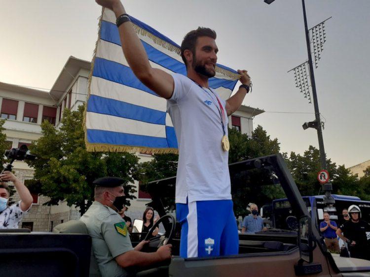 Ο χρυσός Ολυμπιονίκης της κωπηλασίας Στέφανος Ντούσκος με τη γαλανόλευκη στα χέρια χαιρετάει τον κόσμο που τον υποδέχθηκε στα  Ιωάννινα (φωτ.: ΑΠΕ-ΜΠΕ/ΑΠΕ-ΜΠΕ/STR)