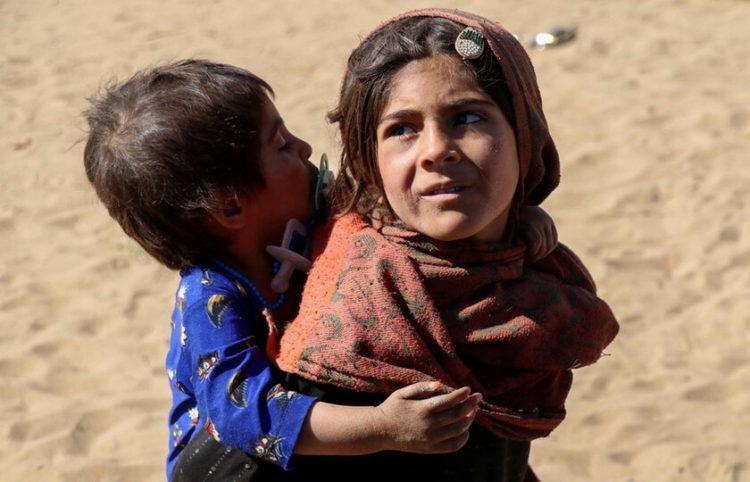 Δύο παιδία πρόσφυγες από το Αφγανιστάν μέσα στις προσφυγικές ροές (φωτ.: EPA/ Muhammad Sadiq)