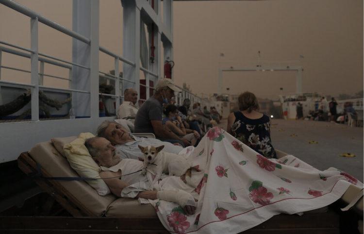 Ο Γεώργιος Λιάκος 89 ετών και η σύζυγός του Παρισσώ Λιάκου 87 ετών κάτοικοι του χωριού Πευκί, περιμένουν μαζί με το σκυλάκι τους Bella, στο κατάστρωμα φέρι μποτ το οποίο βρίσκεται σε αναμονή  στην παραλία του χωριού για να συνδράμει στην εκκένωση του χωριού κατά τη διάρκεια δασικής πυρκαγιάς στην Βόρεια Εύβοια, Κυριακή 08 Αυγούστου 2021 (φωτ.: ΑΠΕ-ΜΠΕ/ Κώστας Τσιρώνης)