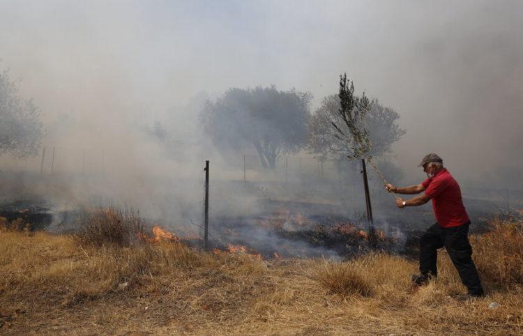 Εθελοντής επιχειρεί στην κατάσβεση της πυρκαγιάς στην Κερατέα, τη Δευτέρα 16 Αυγούστου 2021 (φωτ.: ΑΠΕ-ΜΠΕ/ Αλέξανδρος Βλάχος)