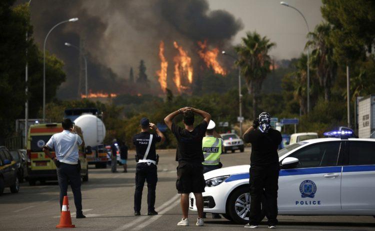 Πολίτες και αστυνομικοί παρακολοθούν από μακρυά τις φλόγες από τη φωτιά που ξέσπασε, σήμερα, σε δασική έκταση στη Βαρυμπόμπη(φωτ.: ΑΠΕ-ΜΠΕ / Γιάννης Κολεσίδης)
