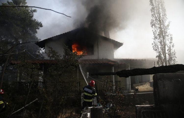 Πυροσβέστες επιχειρούν στην κατάσβεση της φωτιάς στο σπίτι της Κατερίνας και του Χάρη Διγενή, από την πυρκαγιά που ξέσπασε στην περιοχή Κάζα στα Βίλια Αττικής, τη Δευτέρα 23 Αυγούστου 2021 (φωτ.: ΑΠΕ-ΜΠΕ/ Γιάννης Κολεσίδης)