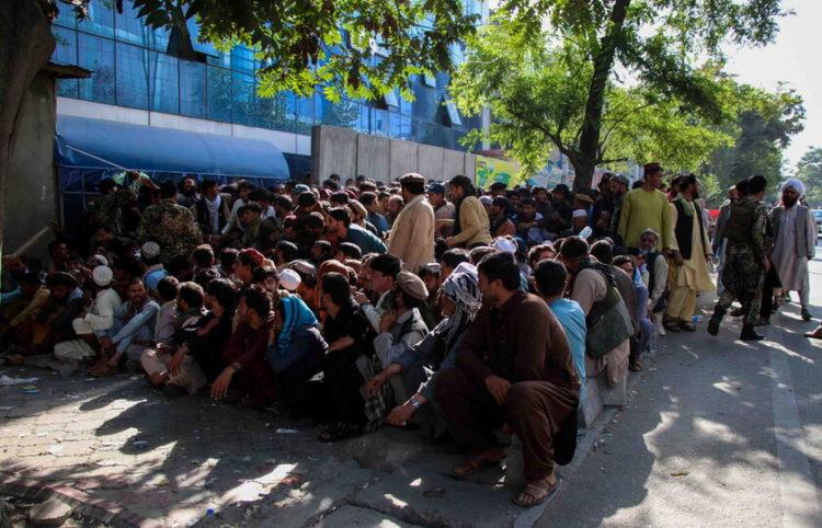 Άνθρωποι περιμένουν μπροστά από τράπεζα στην Καμπούλ (φωτ.: EPA/ STRINGER)