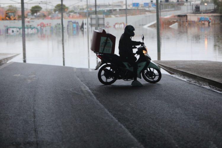 Διανομέας κάνει αναστροφή με το μηχανάκι τους μπροστά από τη γέφυρα όπου ένα λεωφορείο εγκλωβίστηκε και «βούλιαξε» στο νερό που συγκεντρώθηκε, στο ύψος του Δέλτα Φαλήρου από την κακοκαιρία «Μπάλλος» (φωτ.:ΑΠΕ-ΜΠΕ/ΓΙΩΡΓΟΣ ΒΙΤΣΑΡΑΣ)